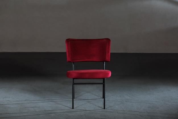 Fauteuil à oreilles rouge confortable dans une pièce aux murs gris