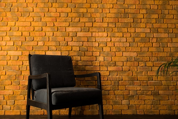 Fauteuil près du mur de brique jaune et palmier dans un pot