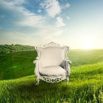 Fauteuil représenté sur l'herbe verte avec paysage au coucher du soleil. belle aube au printemps ou en été. notion de paysage.
