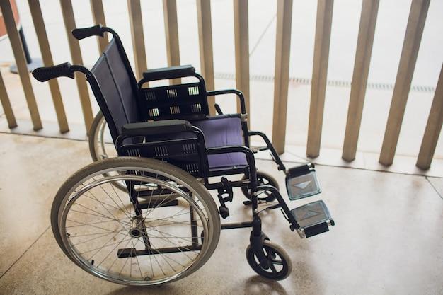 Fauteuil roulant moderne vide près du mur de briques à l'intérieur.