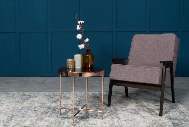 Fauteuil et table d'appoint avec vases en chambre bleue