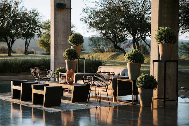 Un fauteuil et une table de jardin décorés avec des vases avec des bougies, des paniers en osier et des plantes diverses.