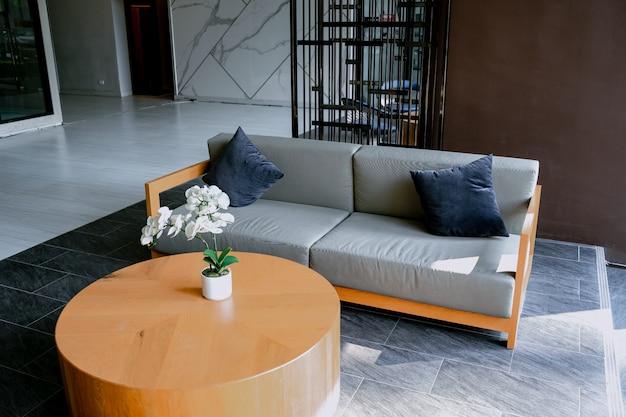 Fauteuil sur un tapis à côté d'un banc avec des plantes dans un loft blanc avec un canapé en bois.