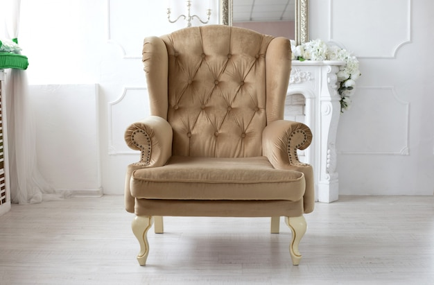 Un fauteuil vintage beige doux se dresse au centre de la salle blanche