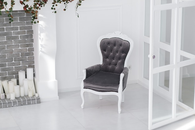 Fauteuil vintage en velours dans une chambre scandinave minimaliste avec cheminée en brique