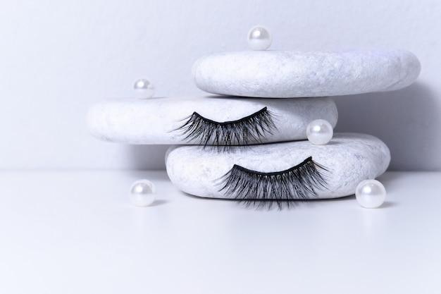 Faux cils artificiels magnétiques et perle sur pierres blanches.