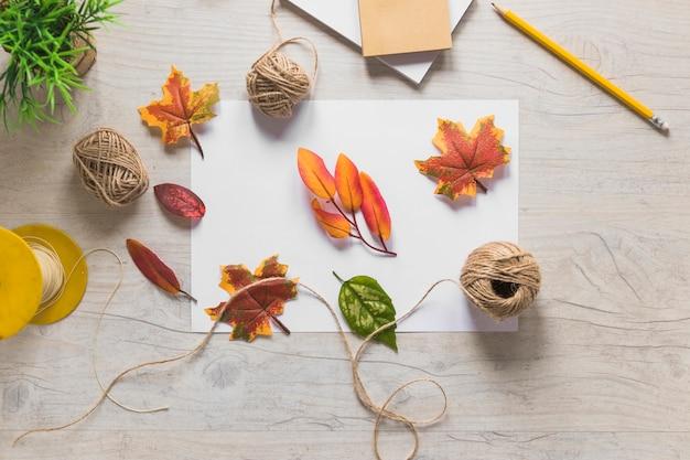 Faux feuilles d'automne avec bobine de fil sur fond texturé en bois