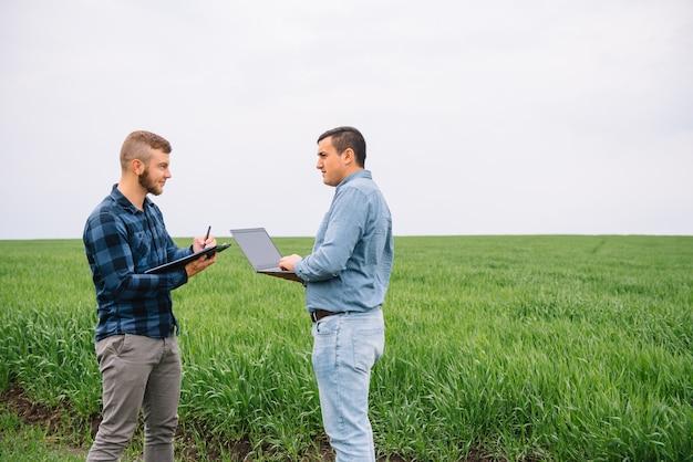Fbusinessmen debout dans un champ de blé et à la recherche sur ordinateur portable