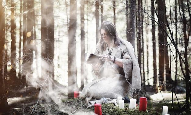 Fée magicienne. un sorcier avec une sphère de verre, un sortilège et un rituel. aîné avec un bâton et une croix dans la forêt. magie noire et blanche. un sort dans le vieux livre.