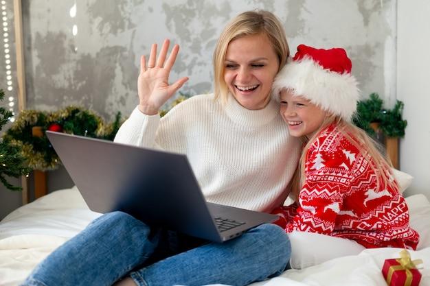 Félicitations à la famille en ligne de noël. sourire de mère et fille blonde européenne à l'aide de mobile