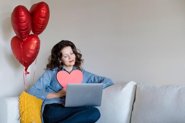 Félicitations en ligne de la saint-valentin. femme souriante à l'aide d'un ordinateur (ordinateur portable) pour le petit ami ou le mari de l'appel vidéo.