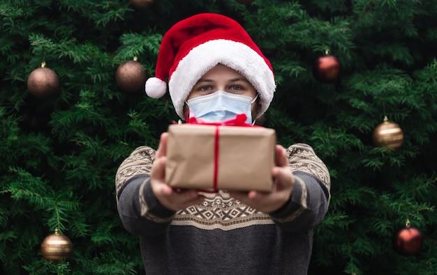 Félicitations de noël de corona. portrait homme portant bonnet de noel et pull en masque médical, donnant une boîte cadeau avec ruban rouge, arbre de noël bokeh sur fond