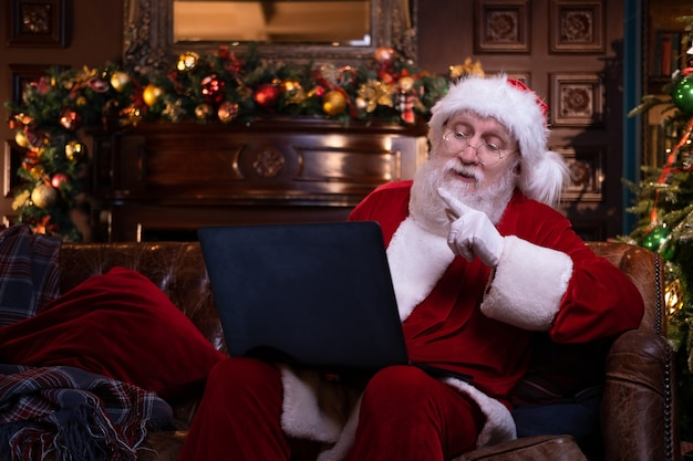 Félicitations de noël en ligne du père noël. père noël à l'aide d'un ordinateur portable