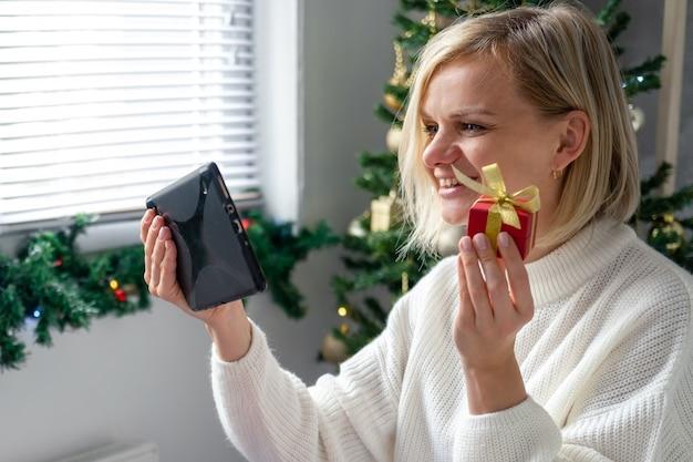 Félicitations de noël en ligne. femme souriante à l'aide de tablette mobile pour les parents et amis des appels vidéo