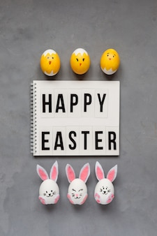 Félicitations de pâques et oeufs de pâques décorés comme des lapins et des poussins sur fond gris.