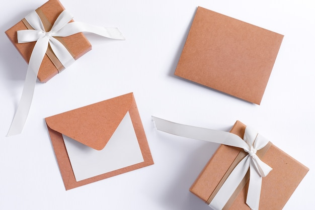 Félicitations à plat de noël avec différents coffrets cadeaux artisanaux, lettre vierge au père noël et enveloppe sur blanc