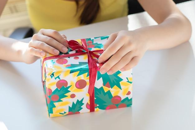 Félicitations pour les vacances. la fille ouvre la boîte avec un cadeau, détache le ruban, enlève le papier d'emballage