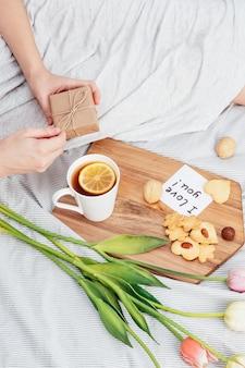 Félicitations à votre femme bien-aimée le jour de la saint-valentin. petit déjeuner au lit pour une fille en chemise de nuit. des fleurs et un cadeau pour le 14 février.