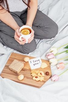 Félicitations à votre fille préférée pour la saint-valentin. petit déjeuner au lit. une femme en pyjama accepte des cadeaux le 14 février.