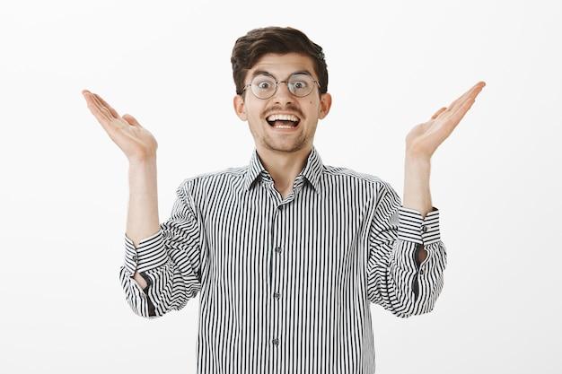 Félicitations, vous gagnez. portrait d'heureux homme caucasien positif avec barbe et moustache, applaudissements, applaudissements avec expression joyeuse satisfaite, debout sur un mur gris