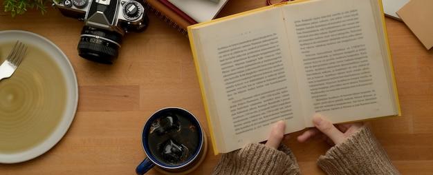 Female college student reading book sur table d'étude en bois avec tasse à café, appareil photo et maquette de plaque