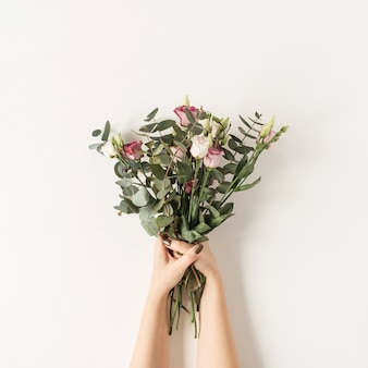 Female hands holding bouquet de fleurs roses colorées contre le mur blanc