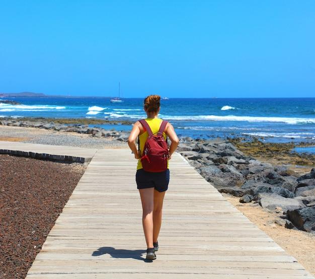 Female hiker walking on catwalk avec paysage spectaculaire de la plage de playa de las americas, tenerife, espagne