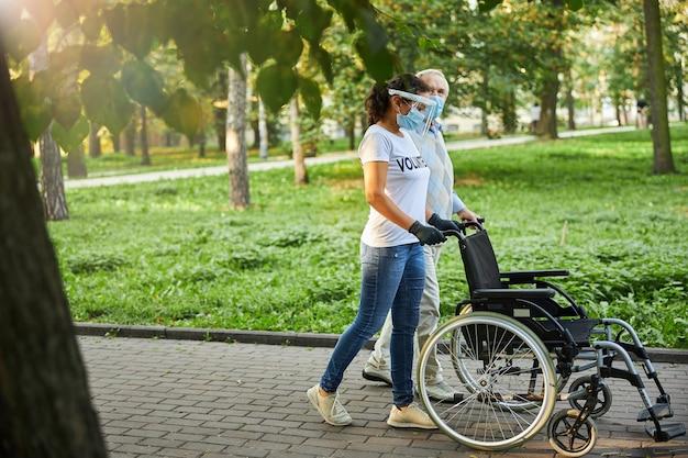Femelle adulte en chemise blanche et jeans passant du temps avec un homme plus âgé à l'extérieur