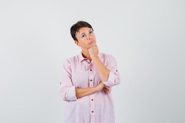 Femelle étayage du menton sur le poing en chemise rose et à la vue réfléchie, de face.