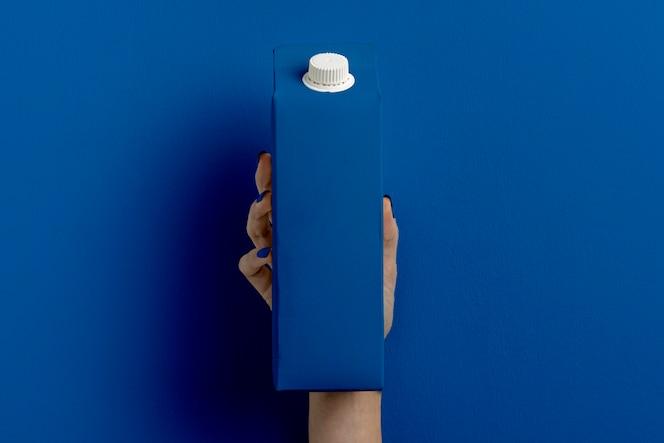 Femelle main tenant le récipient à lait sur bleu classique