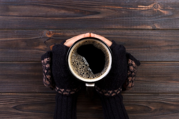 Femelle les mains dans les mitaines tenant une tasse de café sur la table en bois