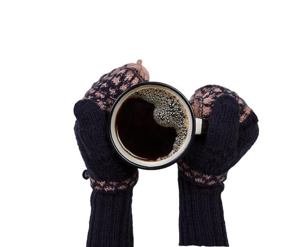 Femelle les mains dans les mitaines tenant une tasse de café