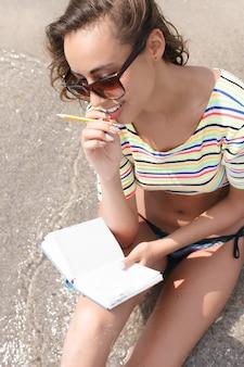 La femelle prend des notes alors qu'elle était assise sur la plage