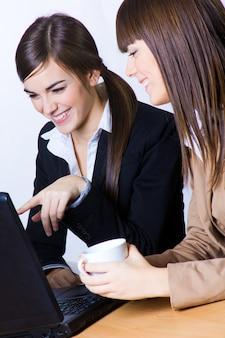 Les femelles gesticulant tout en travaillant sur un ordinateur portable