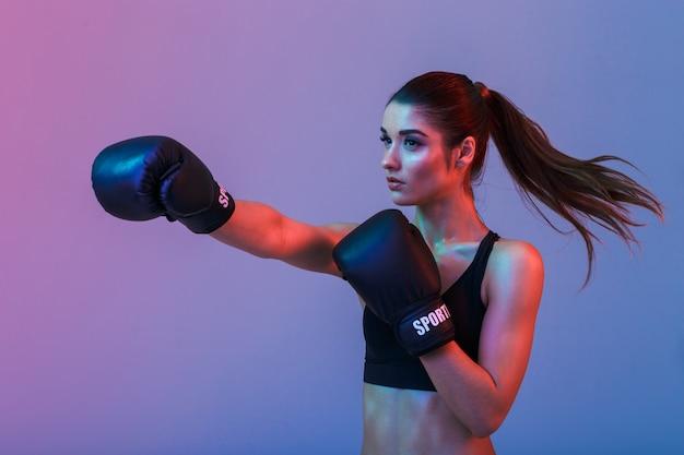 Féminine femme fighter 20s en vêtements de sport et gants de boxe noirs jetant des coups de poing pendant la formation, isolé sur un mur sombre