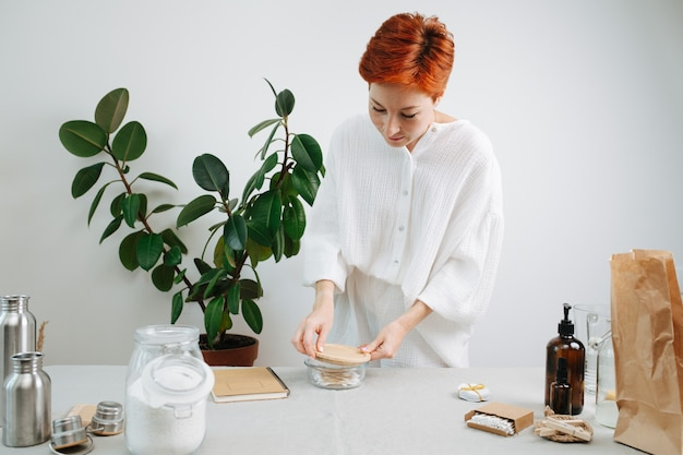 Femme de 30 ans enlevant le couvercle en bois du récipient en verre avec des cotons-tiges écologiques.