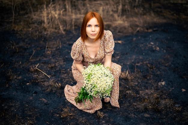 Femme de 40 ans avec un bouquet de fleurs sauvages sur la terre brûlée, concept d'épuisement psychologique