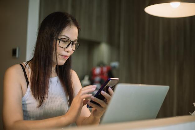Une femme de 40 ans utilise le téléphone et l'ordinateur à la maison.