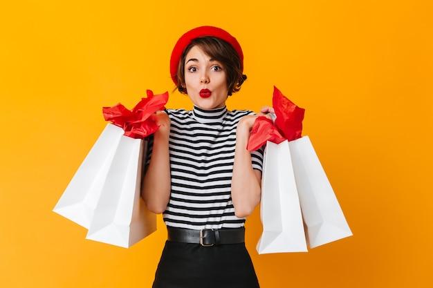 Femme accro du shopping attrayant debout sur un mur jaune