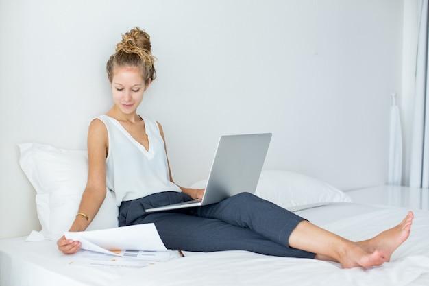 Femme accrochée au lit et travaillant sur ordinateur portable