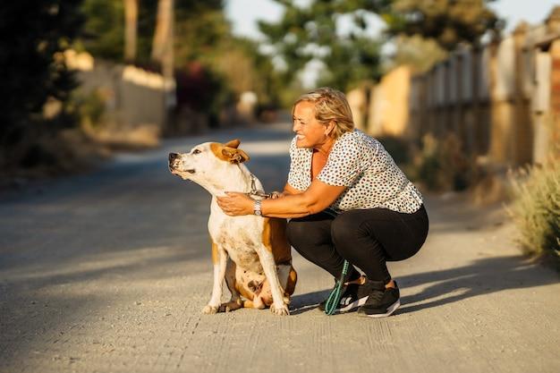 Femme accroupie dans une route non pavée à côté d'un chien qui est distrait