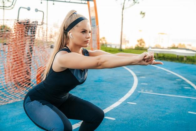Femme accroupie dans la salle de sport en plein air