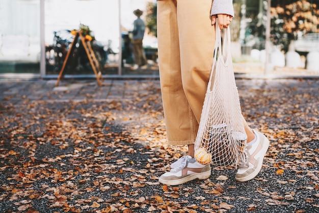 Femme avec achat dans un sac en filet réutilisable en coton sur fond de devanture de magasin zéro déchet