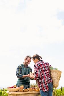 Femme achetant des légumes biologiques d'homme contre ciel