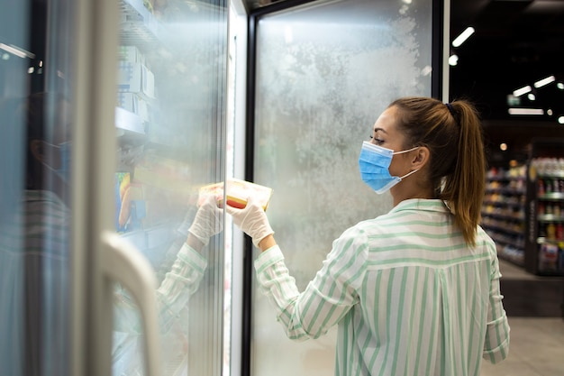 Femme achetant de la nourriture dans un supermarché et se protégeant contre la pandémie du virus corona très contagieuse