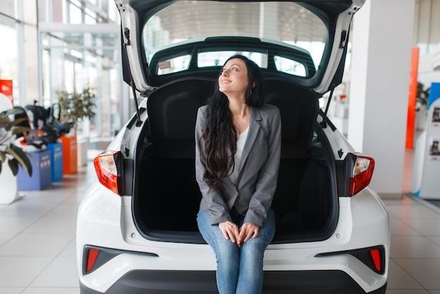 Femme achetant une nouvelle voiture dans la salle d'exposition, dame près du coffre ouvert.