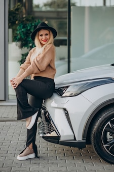 Femme achetant la nouvelle voiture dans la salle d'exposition de voiture
