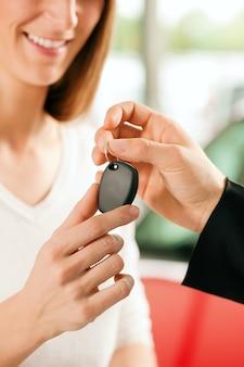 Femme achetant une voiture - clé étant donnée