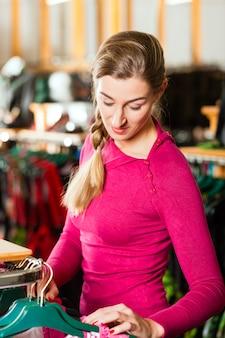 Femme achète du tracht ou du dirndl dans un magasin