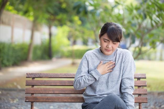 Une femme a des acides de reflux au parc